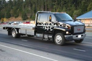 Modern tow truck driving to pick up a car involved in an accident.