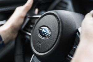 A Subaru steering wheel with hands on it.