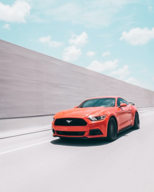 Ford Mustang driving down the road fast.
